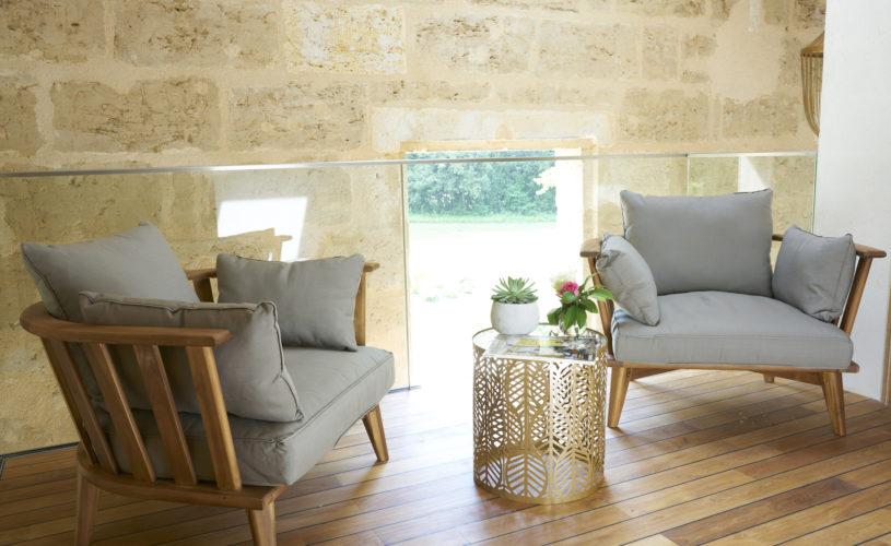 photo du palier, 2 fauteuils gris, table dorée ajourée et décorée, mur en pierre, château Pont Saint-Martin, chambres d'hôtes Pessac Léognan, Bordeaux, dégustation de vin